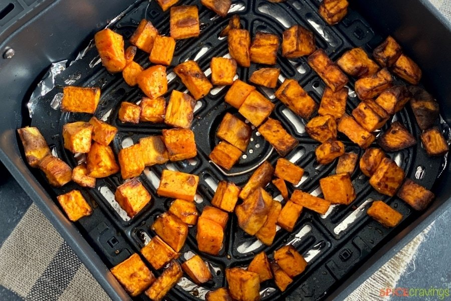 Cubes of roasted sweet potatoes in an air fryer basket