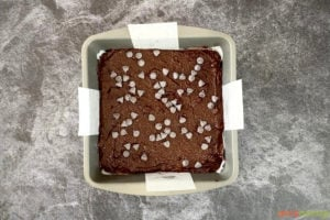 Chocolate chips on top of brownie batter in a tin