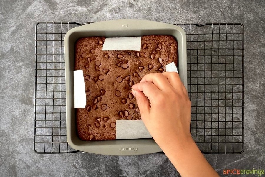 Uncut brownie in a baking tin on a cooling rack