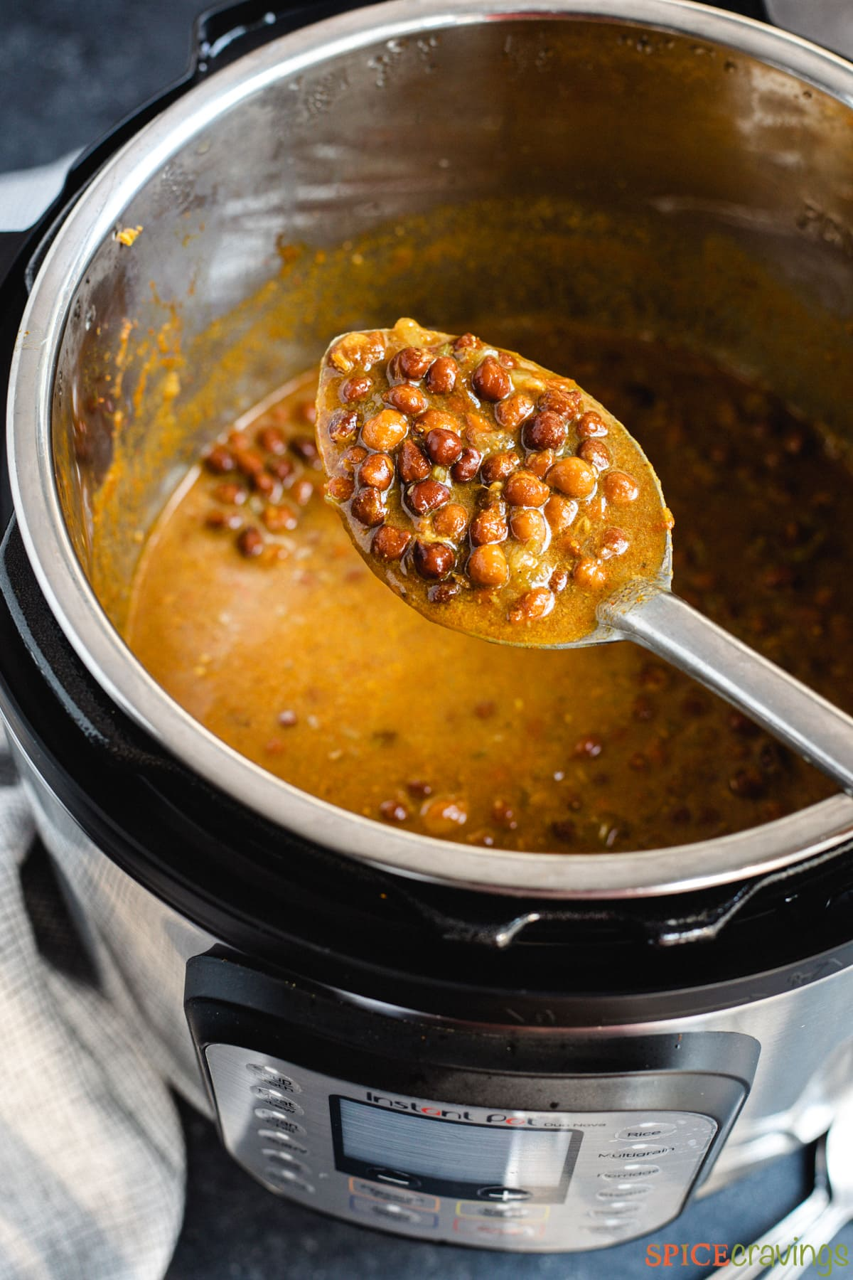 A spoon lifting black chickpeas from an Instant Pot