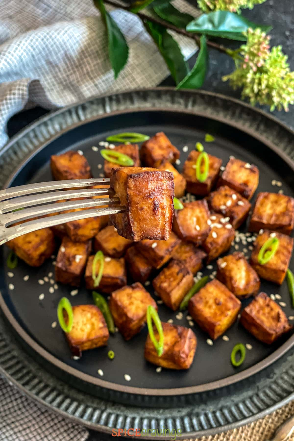 A fork lifting a cube of marinated air fryer tofu from a plate