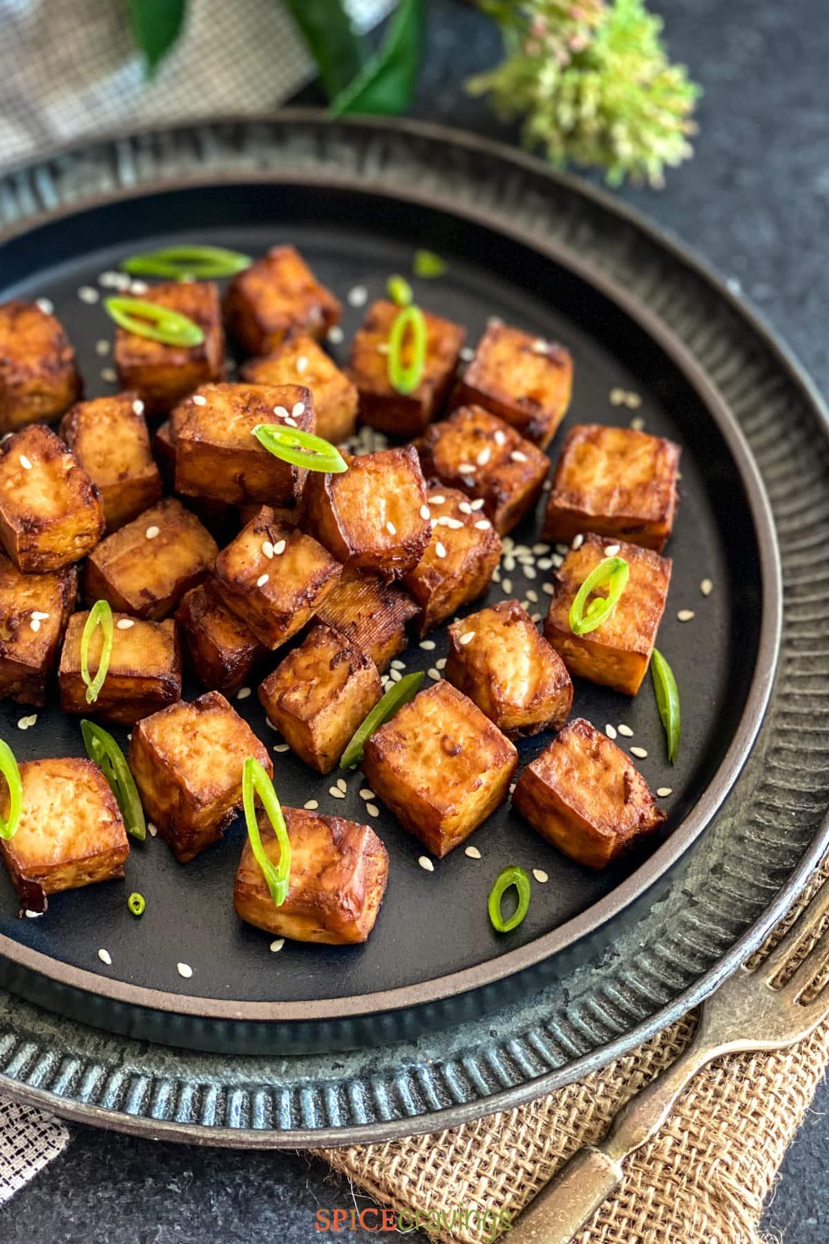 Marinated tofu on a black plate