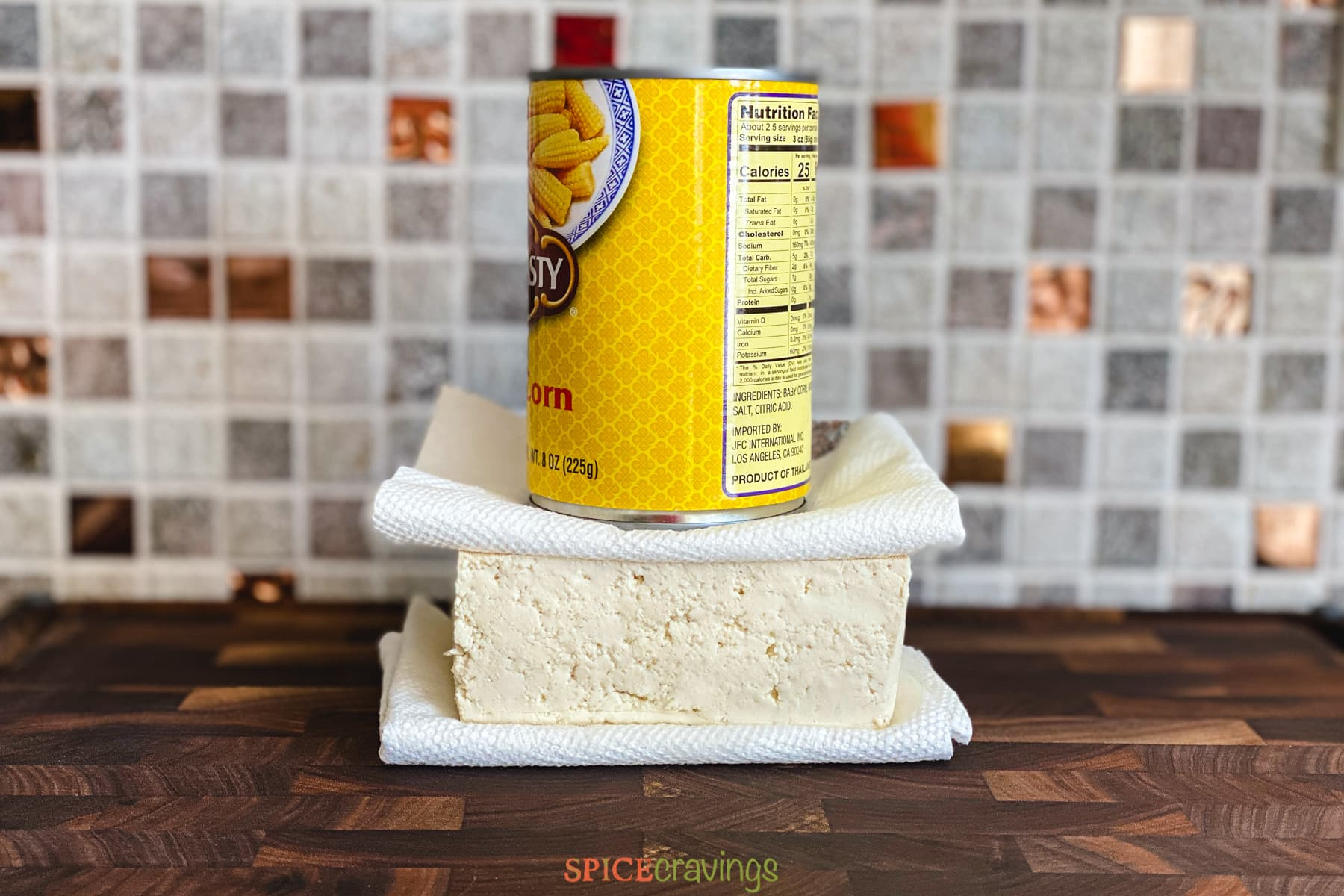 A block of tofu with paper towels underneath and on top, with a can pressing down on top