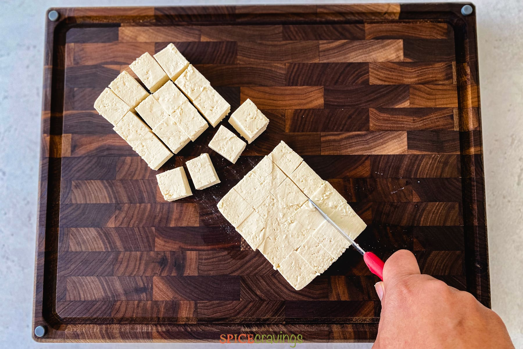 A hand slicing tofu into cubes on a cutting board