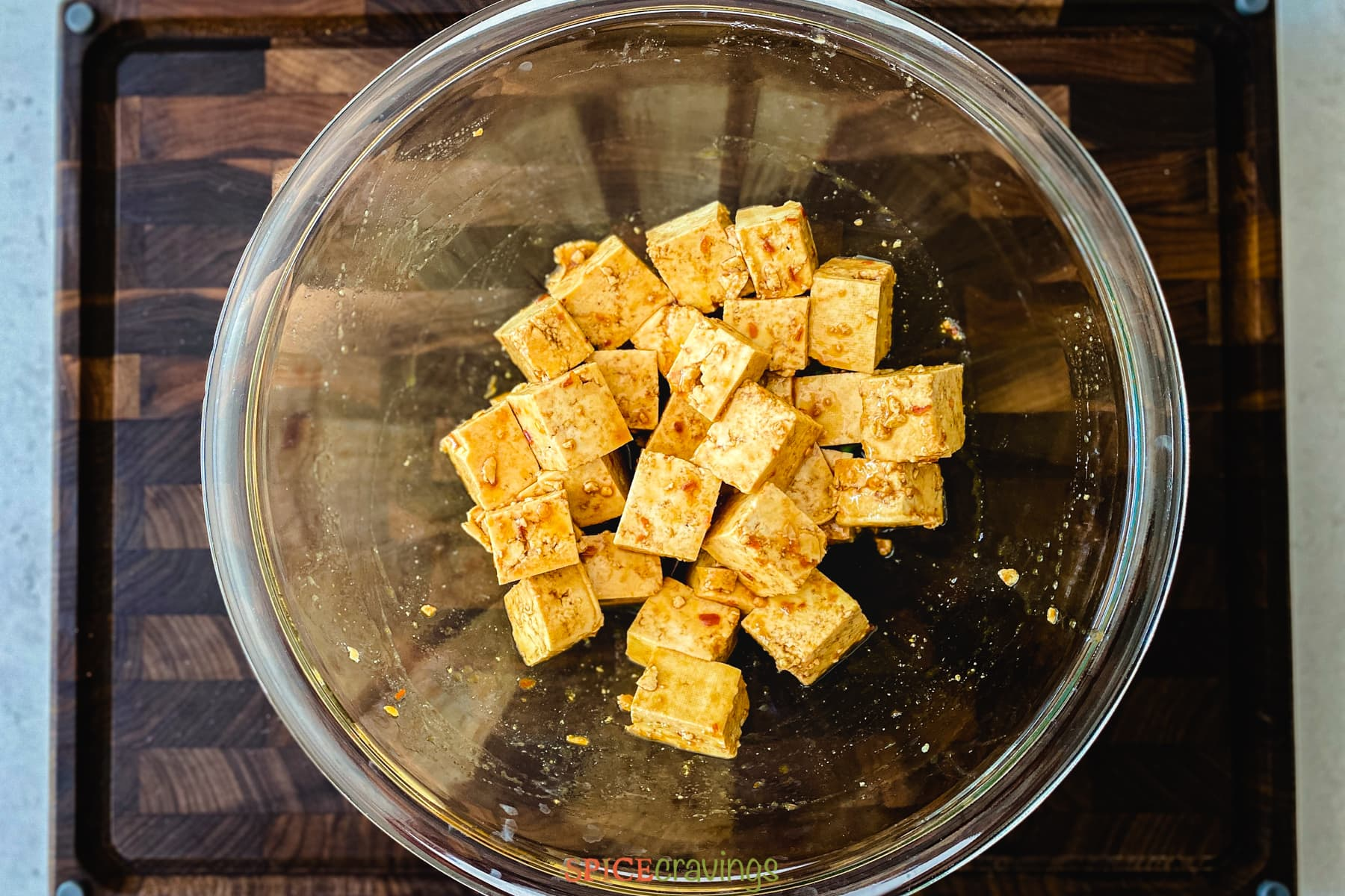 Marinating tofu cubes in a glass bowl