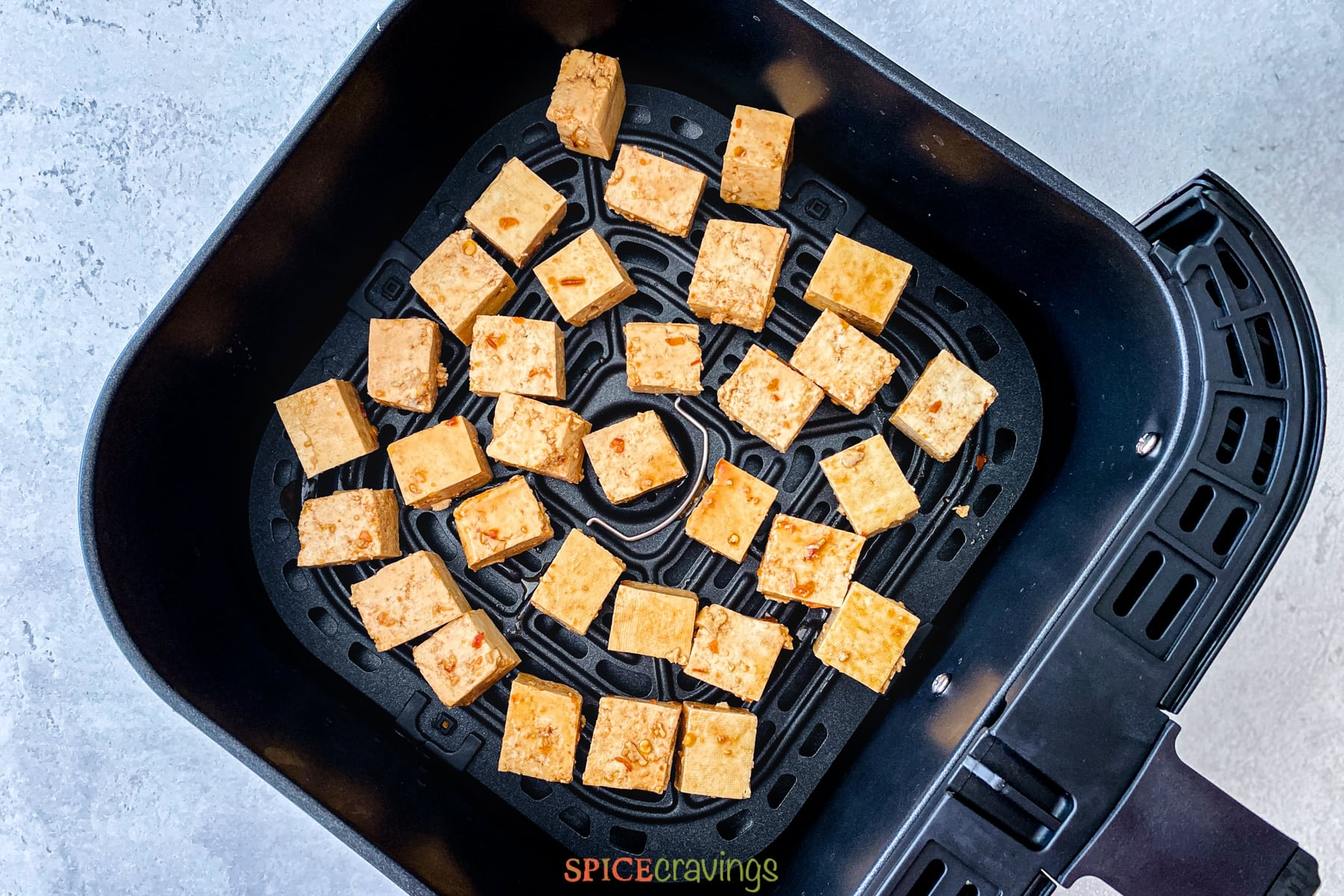 Uncooked tofu cubes in an air fryer basket