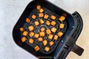Cooked air fryer tofu in an air fryer basket