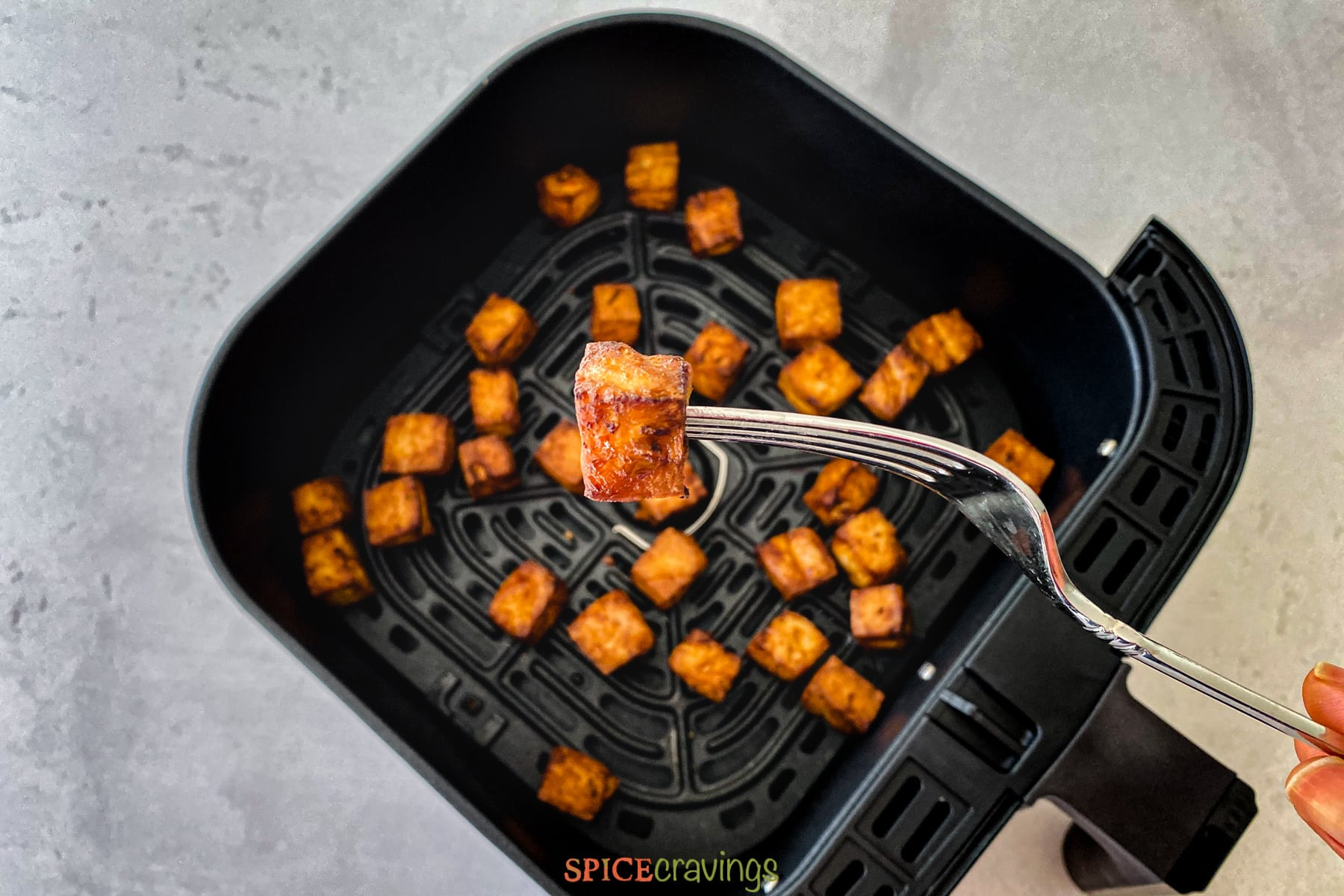 A cube of tofu on a fork to test for doneness