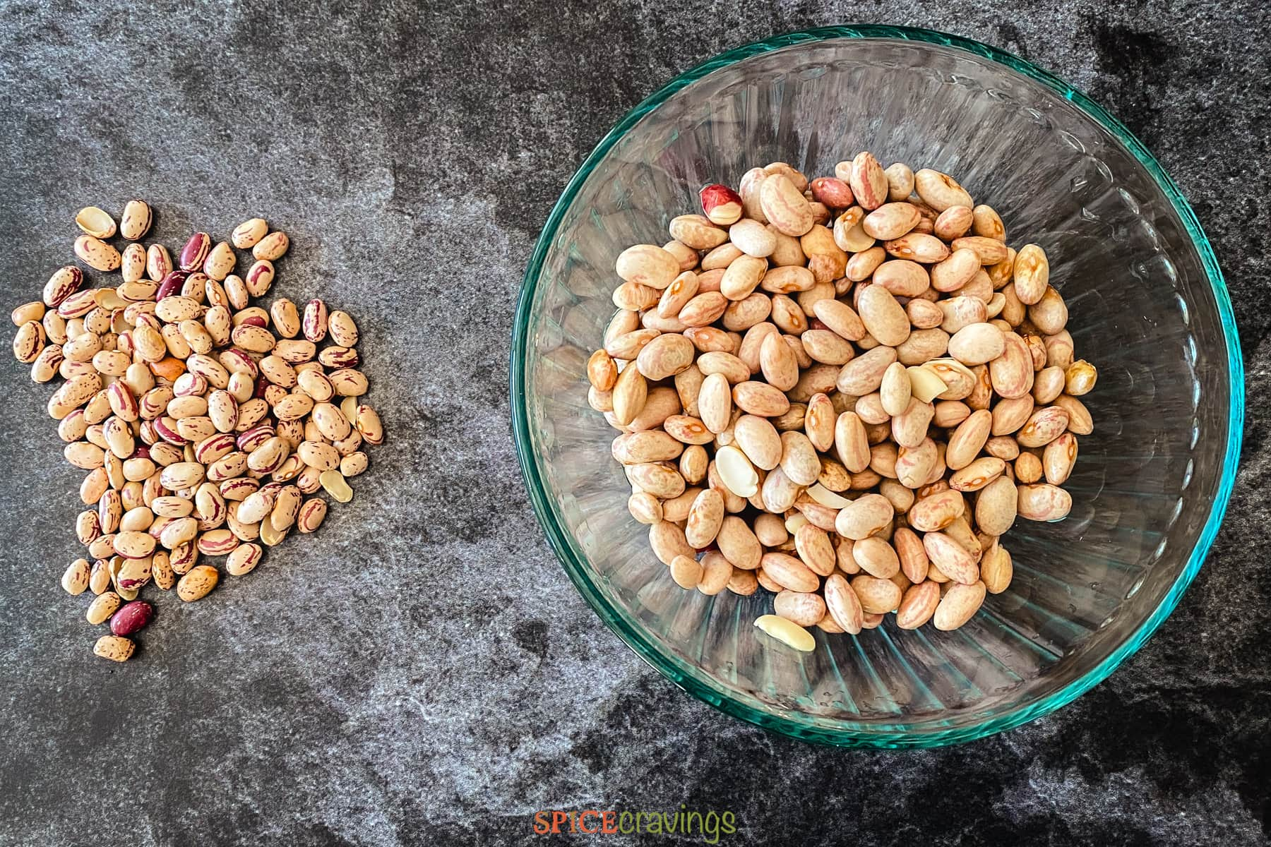 Uncooked pinto beans in a bowl and on a counter