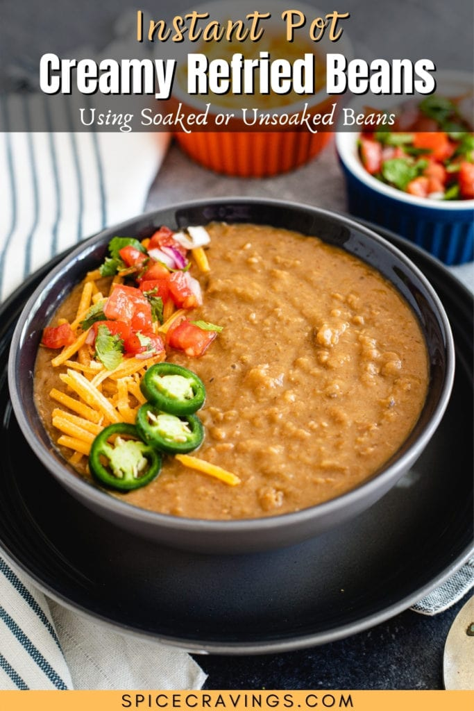 Creamy Refried Beans in a black bowl topped with jalapenos, tomatoes, and cheese