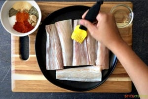 Brushing fish fillets with oil