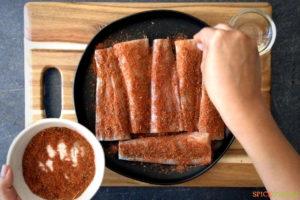 Sprinkling seasoning on fish fillets