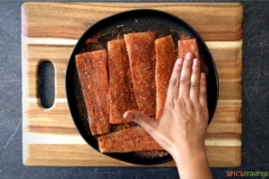 Pressing down the seasoning into the fish
