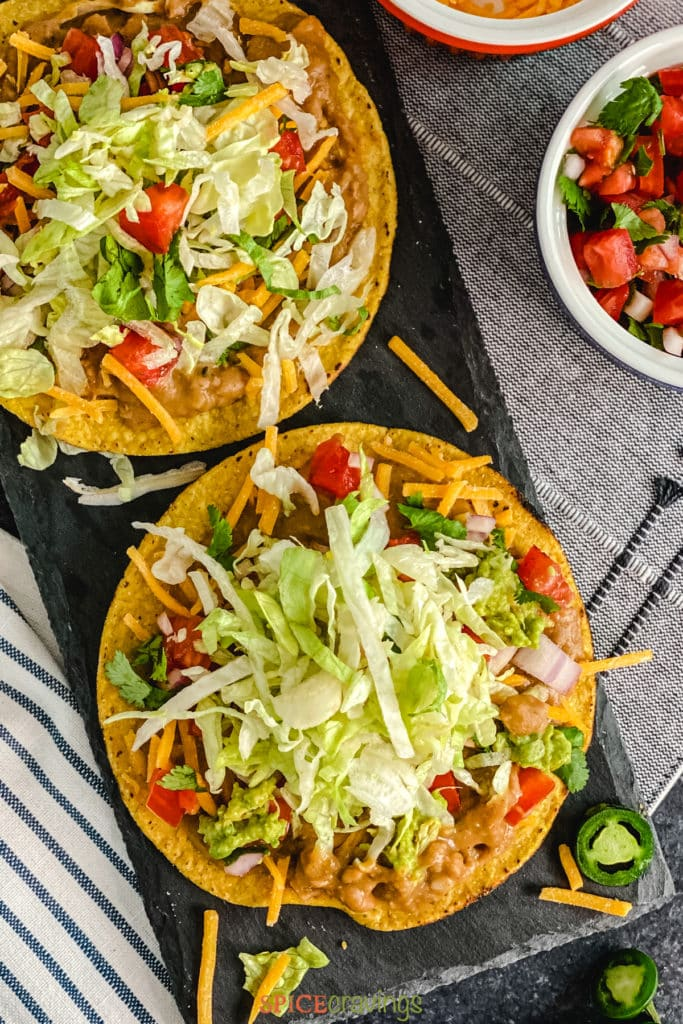 Crispy Tortillas topped with lettuce, beans, tomato and cheese