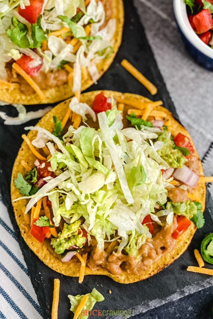 Tostada topped with beans, lettuce on black slate tray