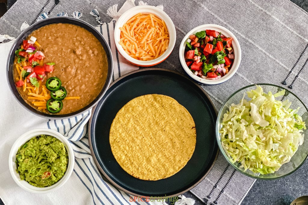Plate of tostada surrounded by beans, cheese, guacamole, salsa, lettuce