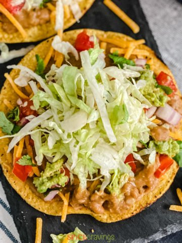 Tostada with lettuce, beans, tomato and cheese
