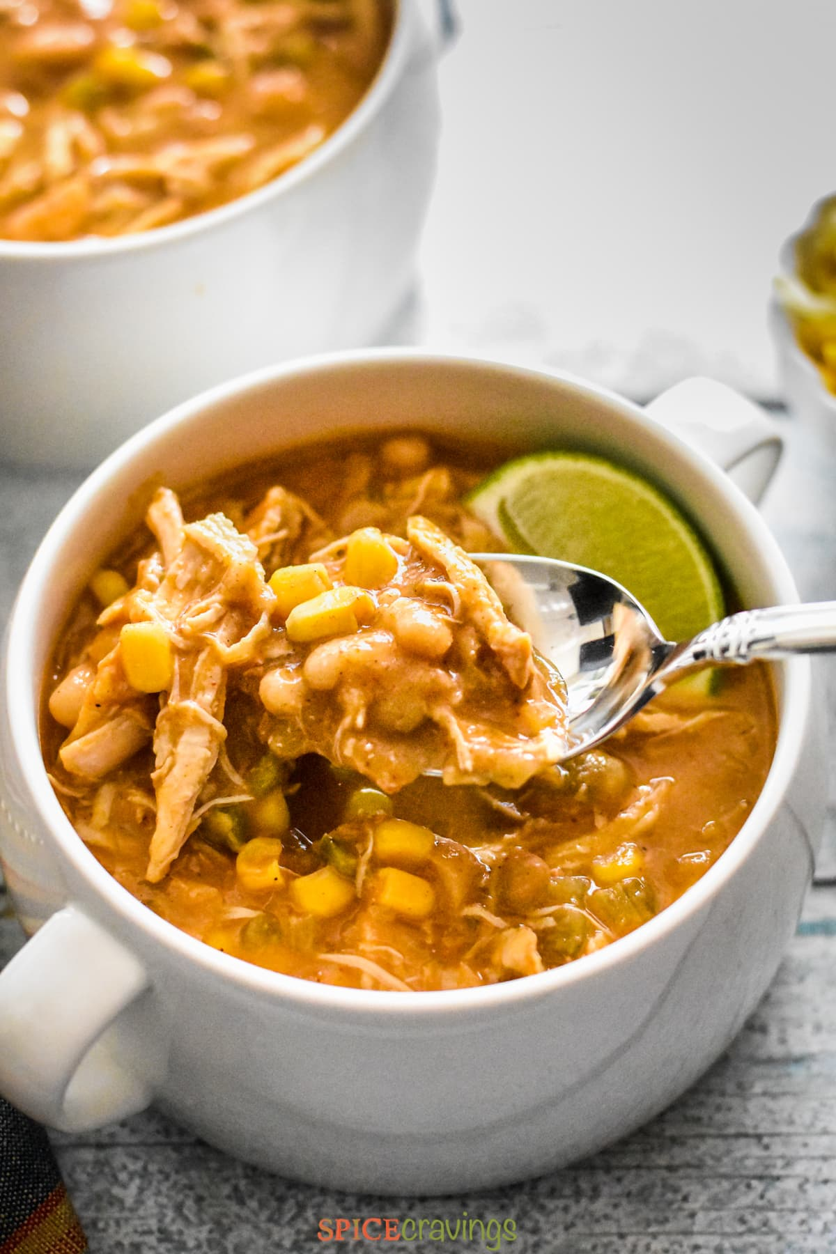 A spoon in a white mug full of Instant Pot White Chicken Chili