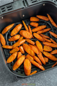 Air fryer carrots spread out in air fryer basket