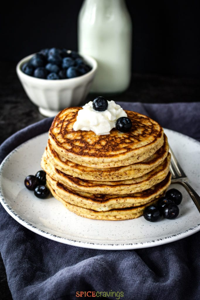 Almond flour pancakes topped with whipped cream and blueberries