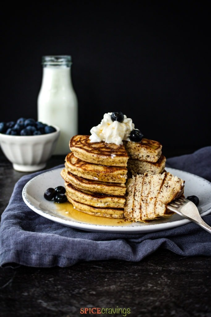 Stack of pancakes with blueberries and milk on the side