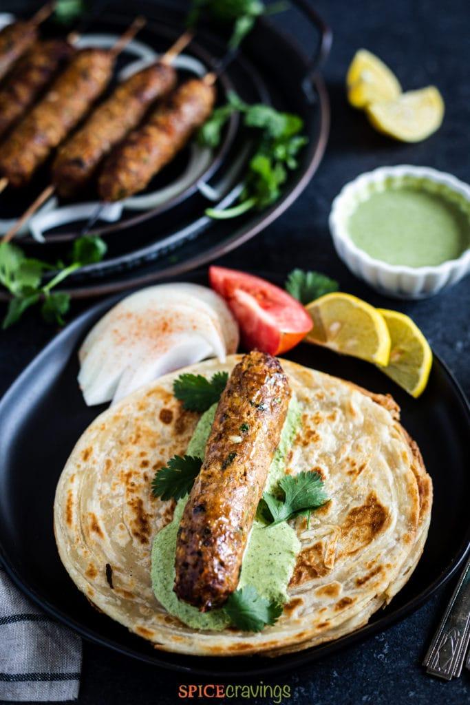 Chicken seekh kebab on a flatbread smeared with chutney
