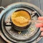 hand scooping spoonful of ground coriander