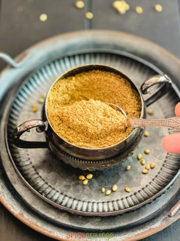 hand scooping spoonful of coriander powder
