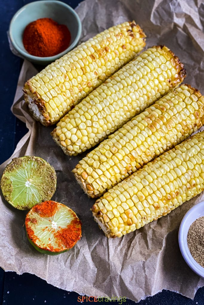 roasted corn on parchment, with spices and lime