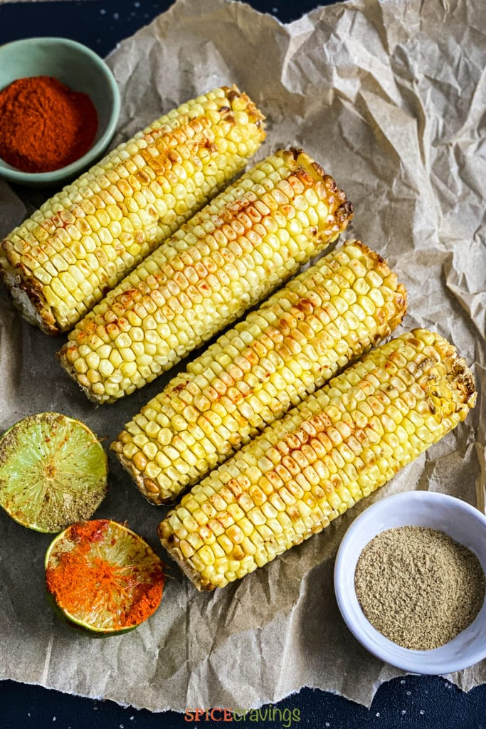 4 ears of roasted corn next to lime halves covered in spices