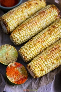Close up of roasted corn ears next to spices and lime halves