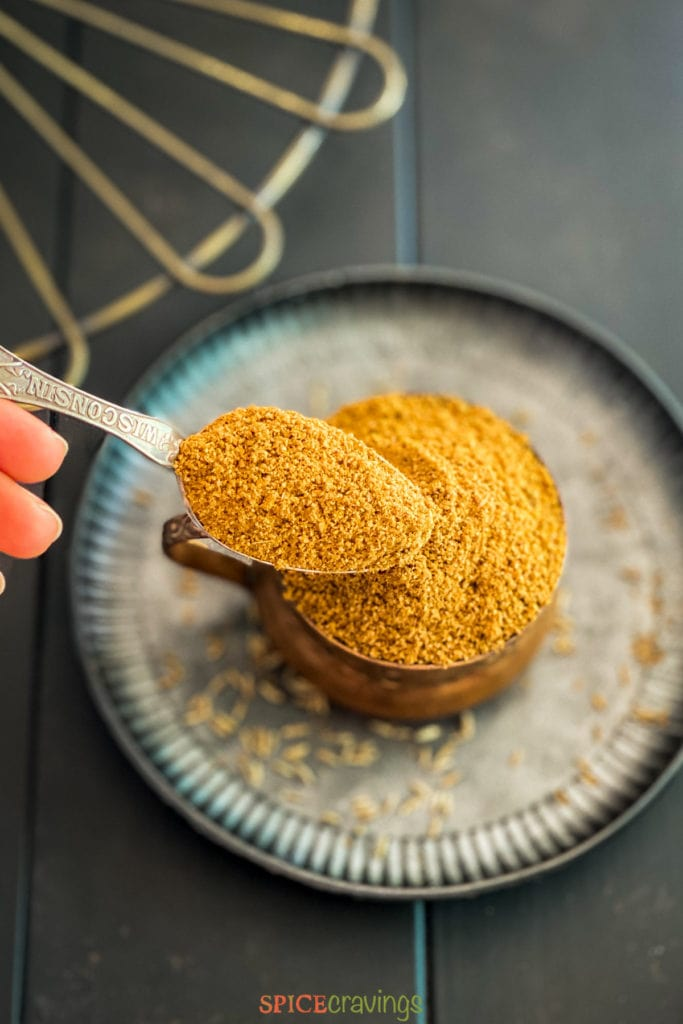 hand scooping spoonful of cumin powder in bowl