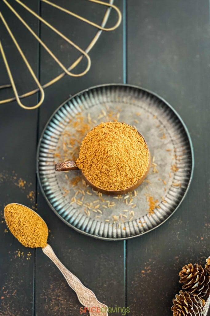 cumin powder in bowl on metal plate