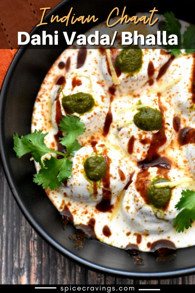 Black bowl with dahi bhalla garnished with green chutney, ginger and cilantro