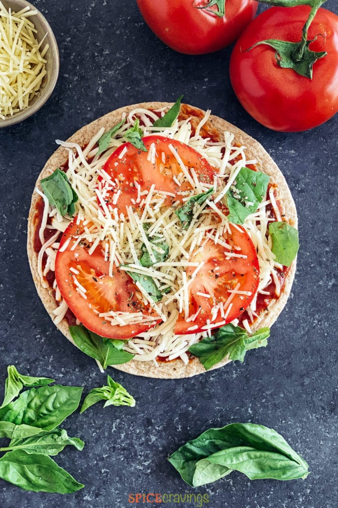 Assembled pizza with tomato, basil and cheese on flatbread