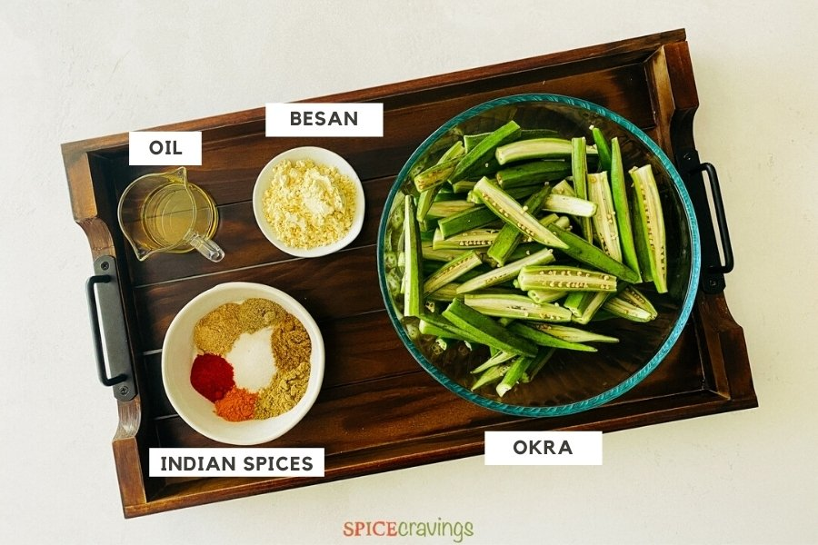 oil, besan flour, Indian spices, sliced okra on wooden board