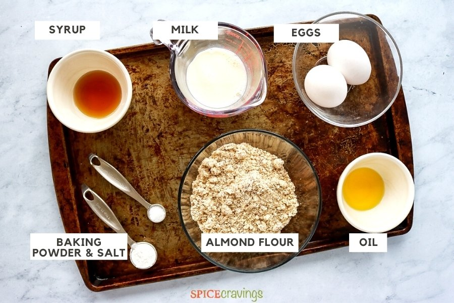 Syrup, milk, eggs, baking soda, almond flour and oil on a baking sheet