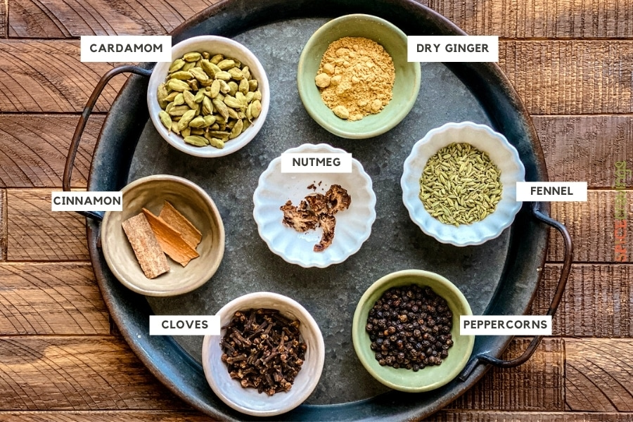 Labeled Whole Indian spices in small bowls on a metal tray