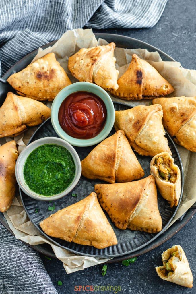 best samosas on serving platter with green and tamarind chutneys