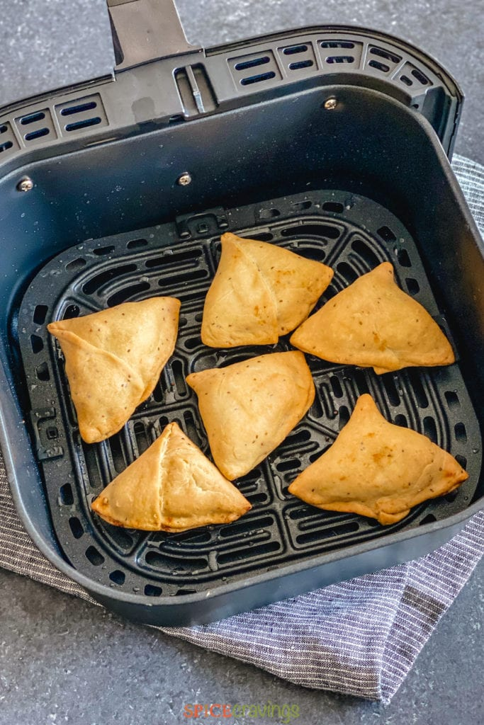 Cooked samosas in air fryer basket