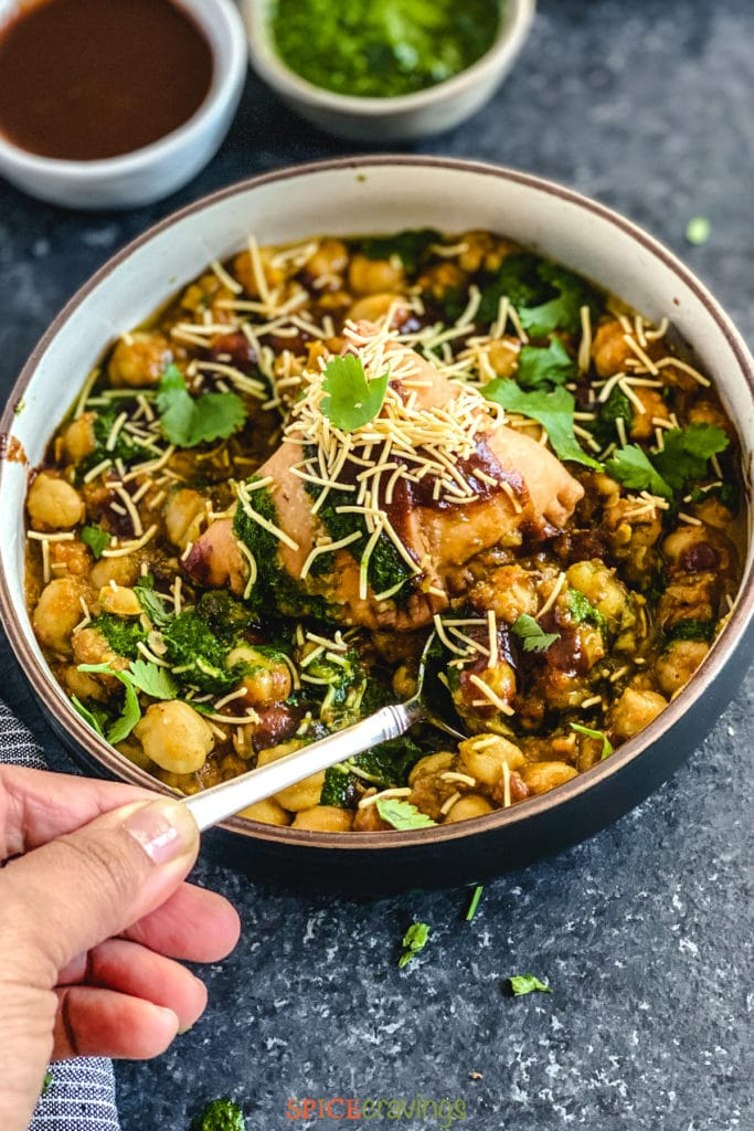 hand scooping spoonful of samosa chaat
