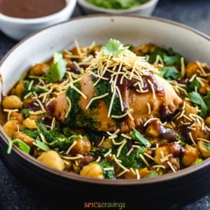samosa and chana masala in bowl topped with chutney and sev