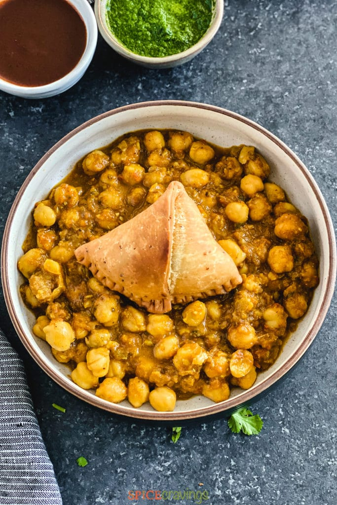 samosa on top of chana masala in bowl