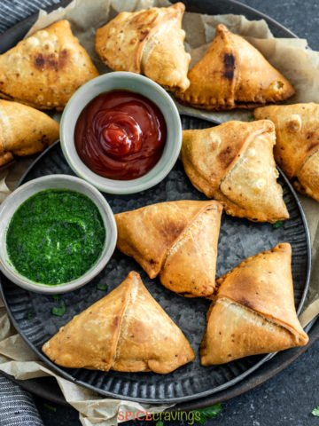 air fried samosas on serving platter with green and tamarind chutneys