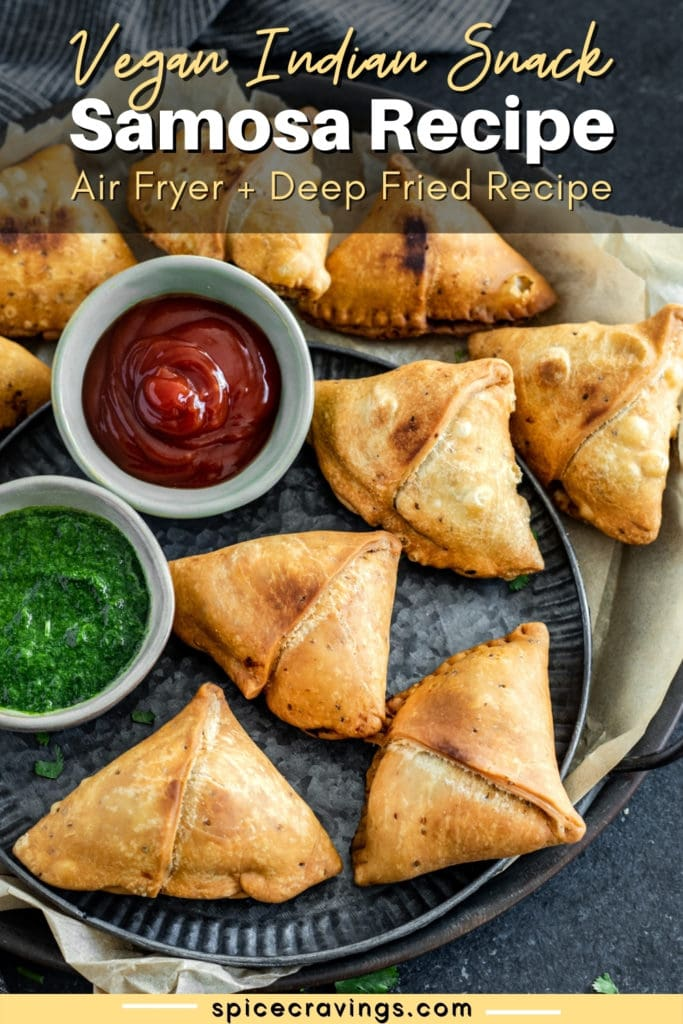 Samosas on a metal plate with two bowls of chutney and ketchup