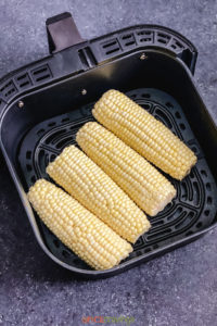 4 ears of corn placed in the air fryer basket
