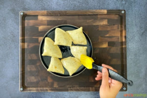 brushing samosas with oil