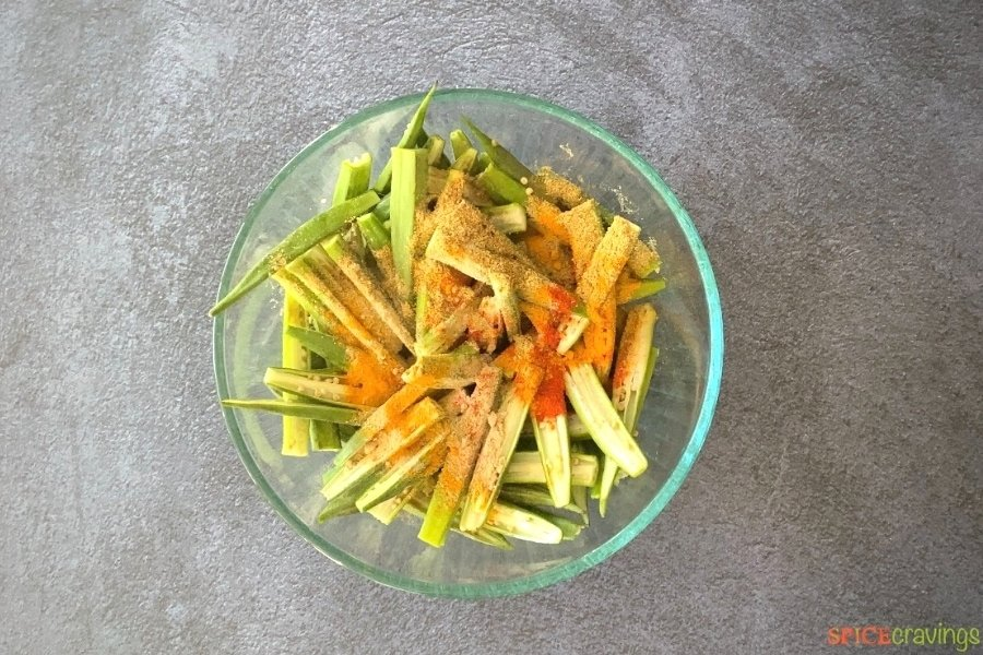 sliced okra, Indian spices and besan flour in glass bowl