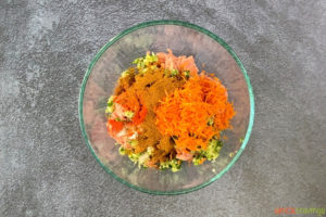 Ground meat, shredded carrots, spices in a glass bowl