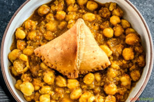 samosa on top of chole in bowl